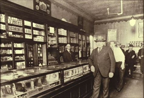 About 1924. First Ward Cigar Store, southwest corner Main and B Streets. A.W. Robinson, proprietor on left, ___Greenfielder (in front), unidentified, Drury Poll and Henry Brown/Lane Library Cummins Collection